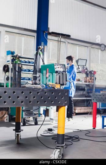 Germany, Neukirch, Apprentice working on machine - Stock-Bilder