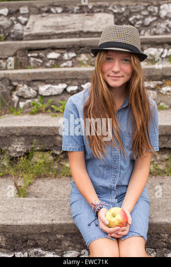 Teenage girl hipster in a hat and an apple in his hands, outdoors. - Stock Image