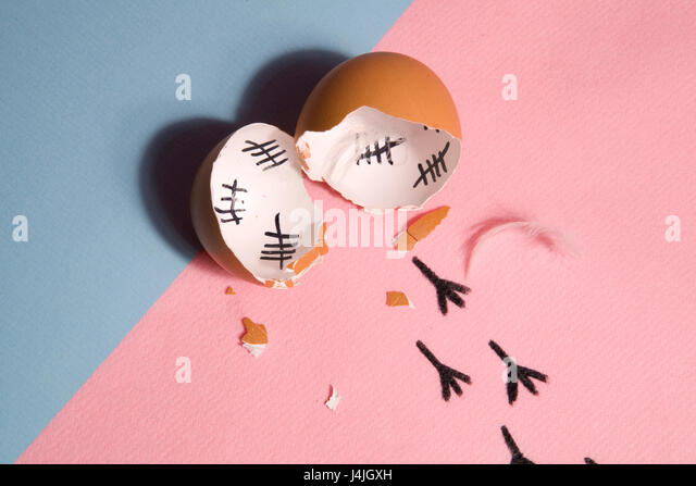 The counting of the days on a broken egg with footprint on a pink and blue background - Stock Image