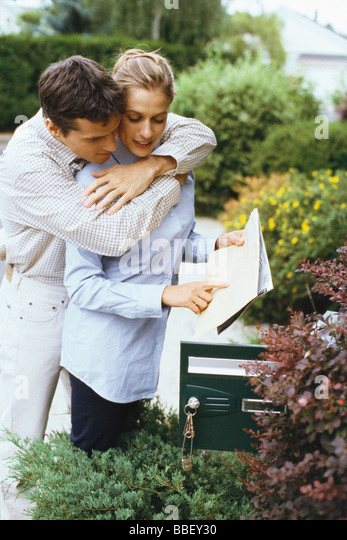 Couple checking mail together, man embracing woman from behind - Stock-Bilder