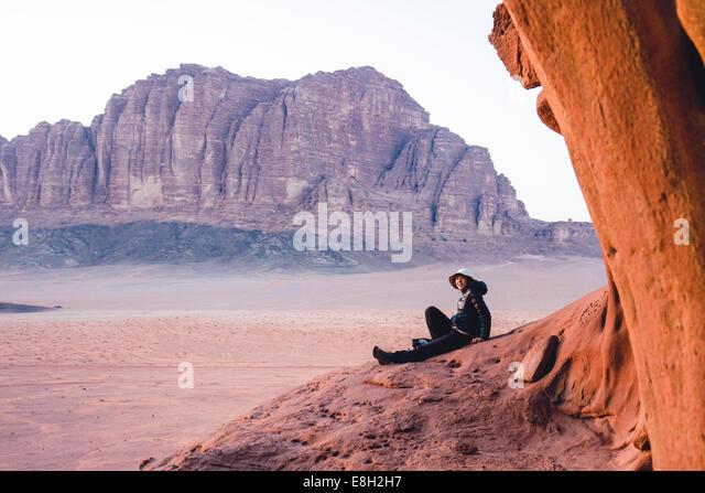Jordan, Japanese woman sitting on top of a rock in Wadi Rum - Stock Image