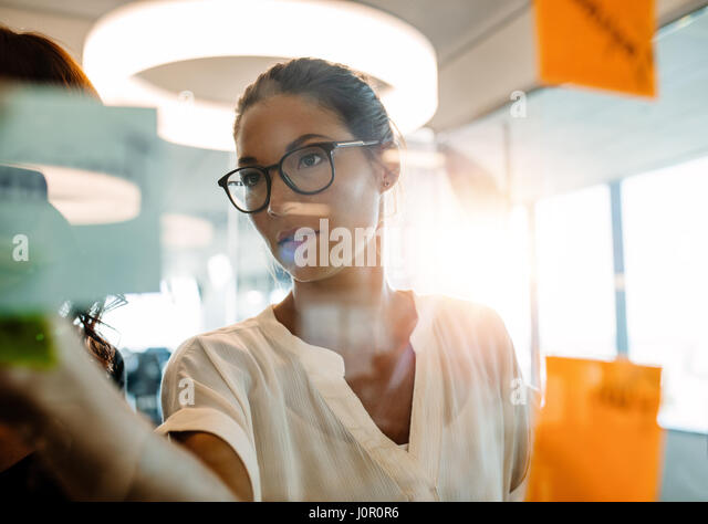 Asian businesswoman looking over a post it note wall and brainstorming. Mature woman standing at the office behind - Stock Image