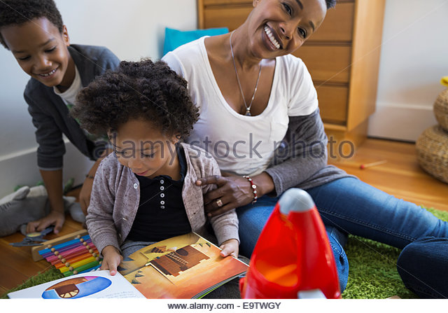 Mother and children reading story in bedroom - Stock Image