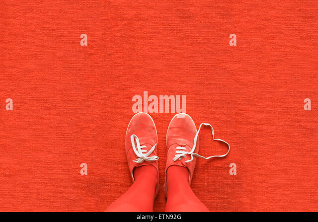 Knees down view of a woman's legs with a heart made out her shoelaces - Stock-Bilder