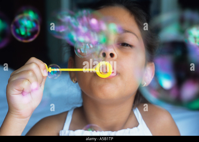 Young Child Blowing Bubbles USA - Stock Image