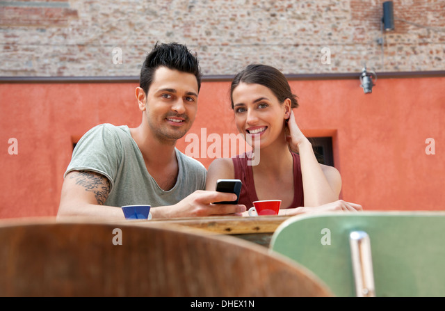 Couple with smartphone outside cafe, Florence, Tuscany, Italy - Stock Image