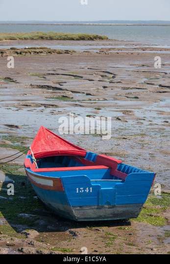 A small painted wooden fishing boat beached on the shores of Sado Estuary outside Carracqueira village on the Algarve. - Stock Image