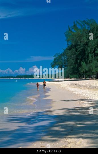 Seven Mile Beach older mature couple walking beach Grand Cayman Island - Stock Image