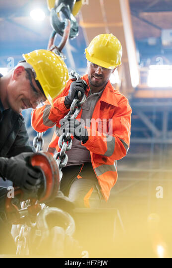 Steel workers with crane hook in factory - Stock Image