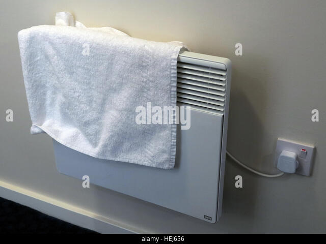 Drying towels or clothes on electric convection heaters,danger of fire - Stock Image