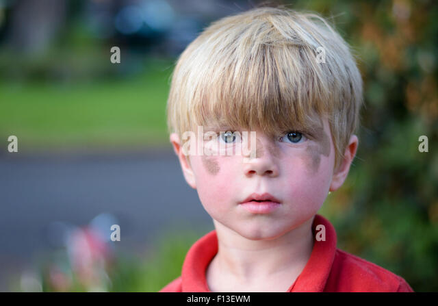 Portrait of a boy with dirt on his face - Stock Image