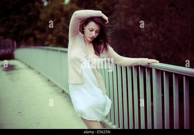 Young woman standing at the railing of a bridge - Stock Image