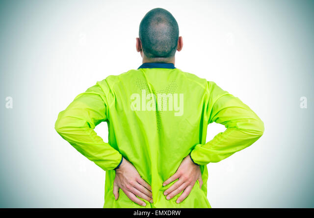 a young caucasian sportsman wearing sport clothes with his hands in his back because of his low back pain - Stock Image