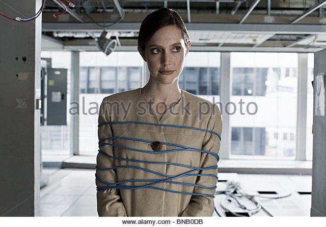 Businesswoman tied up in cables - Stock Image