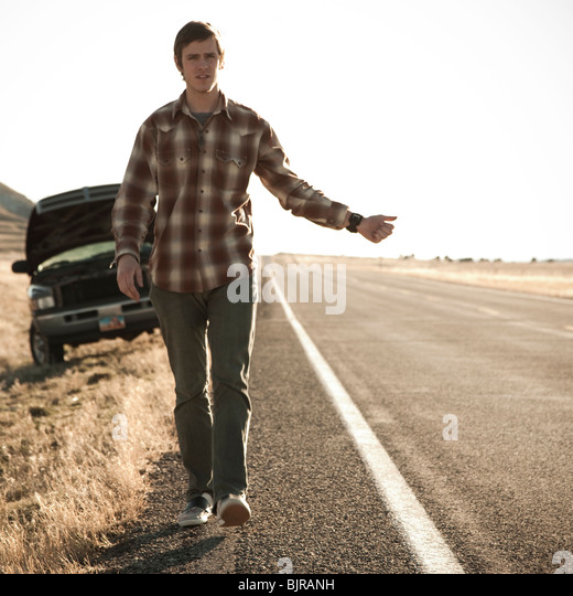 USA, Utah, man hailing on road, broken car in background - Stock Image