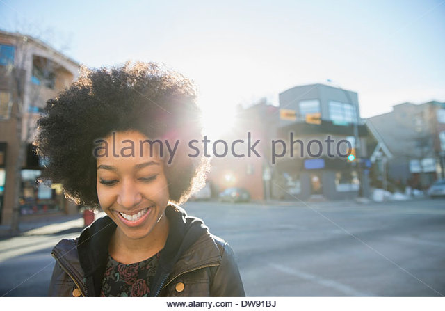 Smiling woman looking down on city street - Stock Image