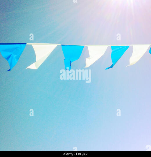 Bunting hanging against blue sky - Stock Image