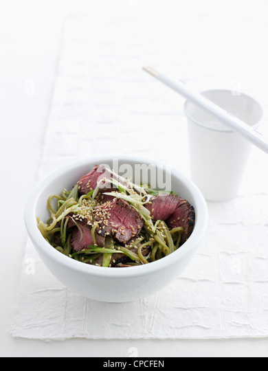 Bowl of beef and green tea noodles - Stock Image