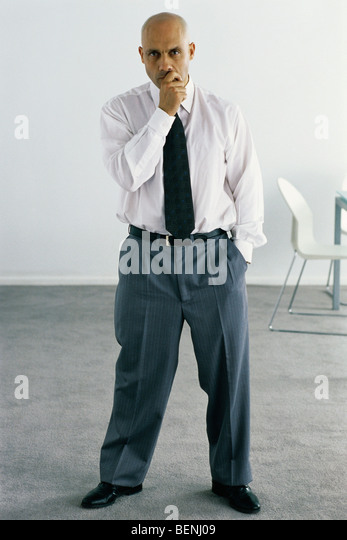 Business executive standing in office, looking thoughtfully at camera, full length portrait - Stock Image
