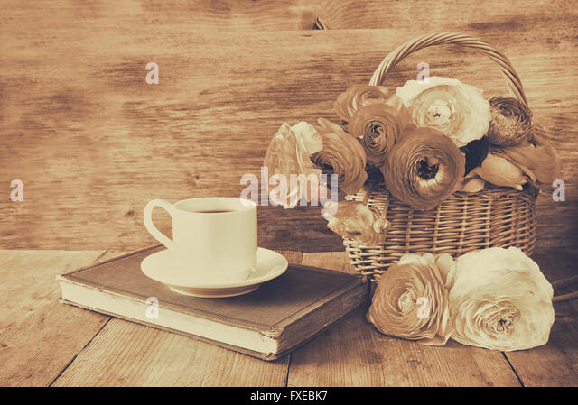 cup of coffee next to old book next to flowers on wooden table. vintage filtered and toned - Stock Image