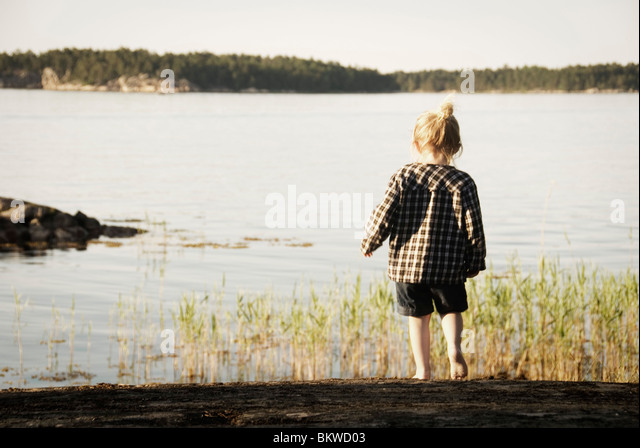 Little girl by the lake - Stock Image