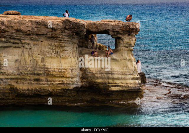 Tourists on the rock cave formations at Cape Greco, Cyprus. - Stock Image