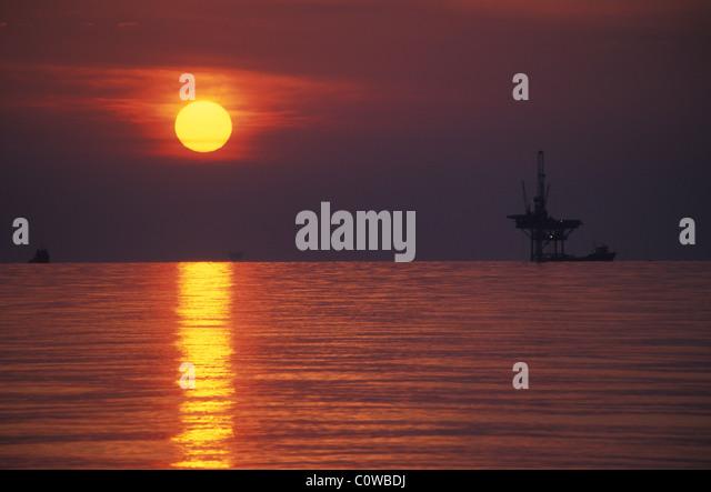 An off-shore oil rig at sunset. - Stock-Bilder