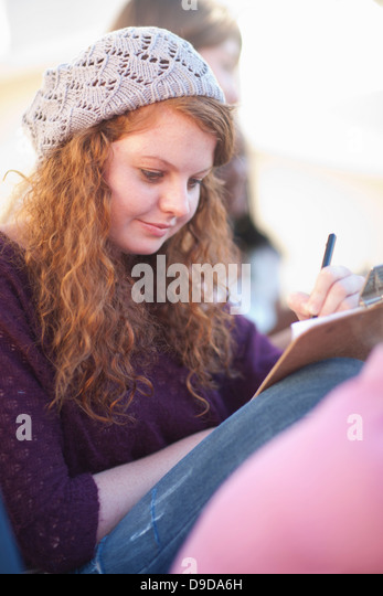 Young woman wearing knit hat writing on clipboard - Stock Image