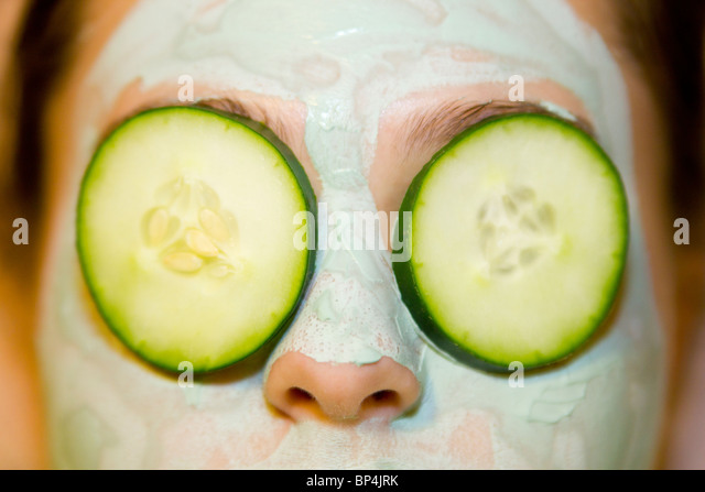 Girl with Green Facial Mask and Cucumber Slices over Eyes - Stock-Bilder