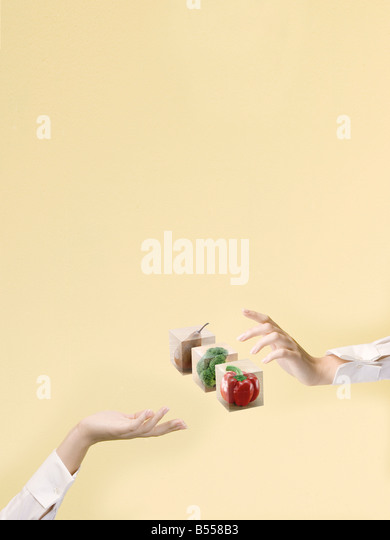 hands passing food blocks to each other like the Sistine chapel - Stock Image