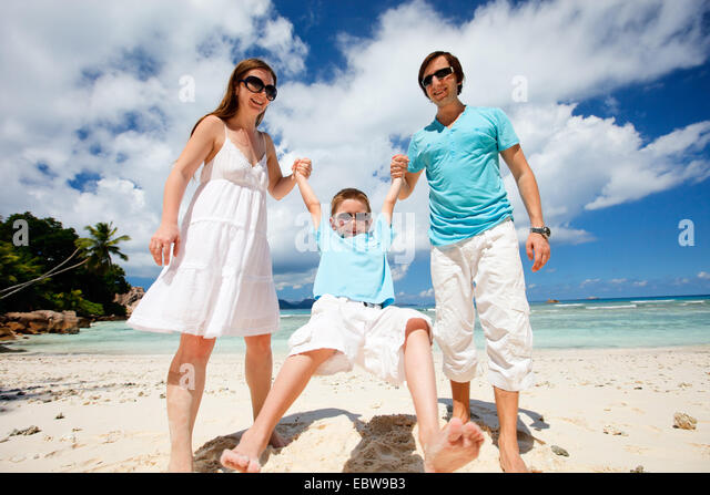 happy young family on tropical beach - Stock Image