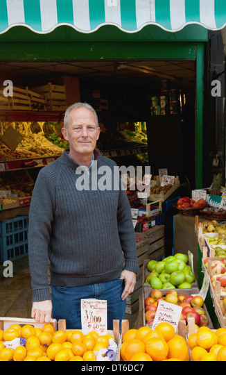 Greengrocer in front of his stall - Stock Image