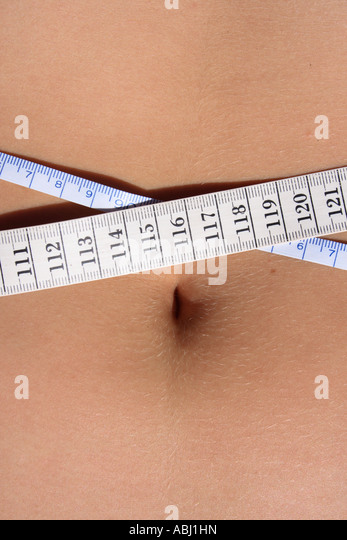 young woman measuring waist. Photo by Willy Matheisl - Stock Image
