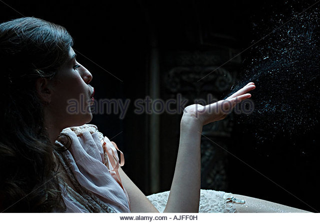 Woman blwoing dust from hand - Stock Image