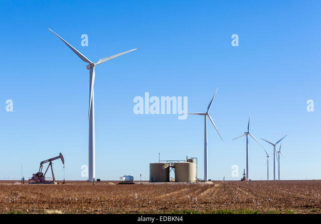 Oil well next to wind turbines outside Midland, Texas, USA - Stock Image