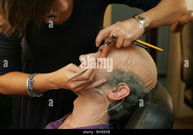 Makeup artist applying eyeliner to an actor. - Stock Image