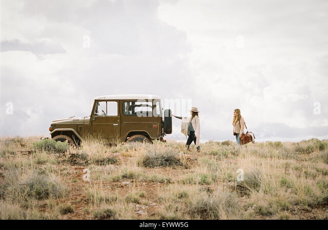Two women by a jeep in open space, loading up for a road trip. - Stock Image