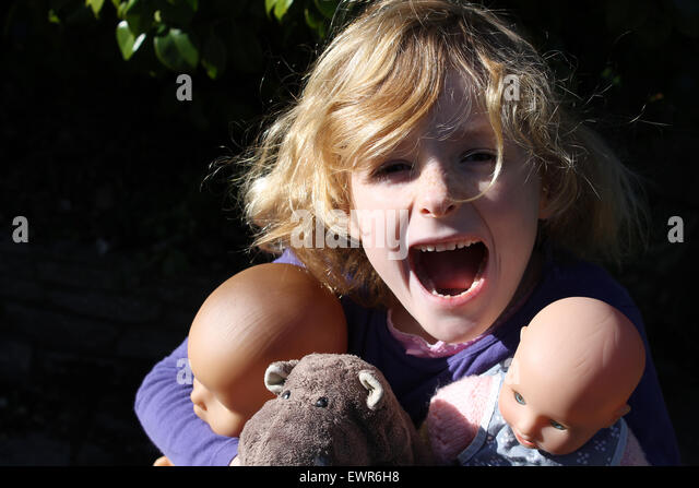 A six year old girl screams with joy as she hugs her most valuable posessions: two dolls and a stuffed hippopotamus - Stock Image