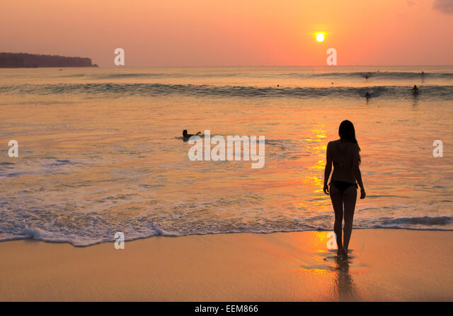 Indonesia, Bali, Woman watching sunset on beach - Stock Image