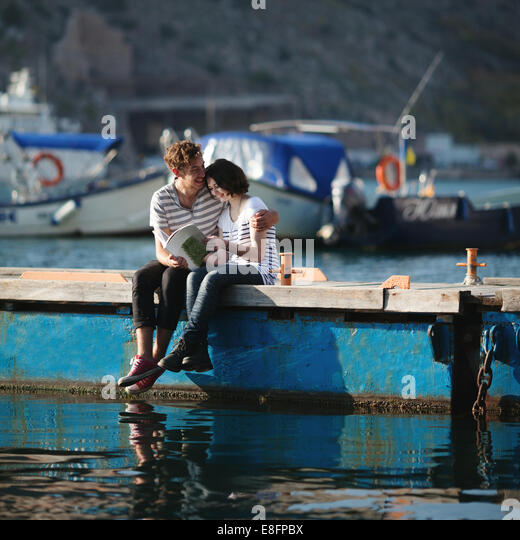 Teenage couple (14-15) sitting on jetty, embracing - Stock-Bilder