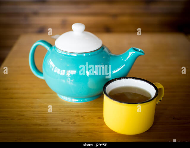 A yellow cup of peppermint tea and a turquoise teapot at the Drift Sidewalk Café and Vista Lounge in Saskatoon, - Stock Image