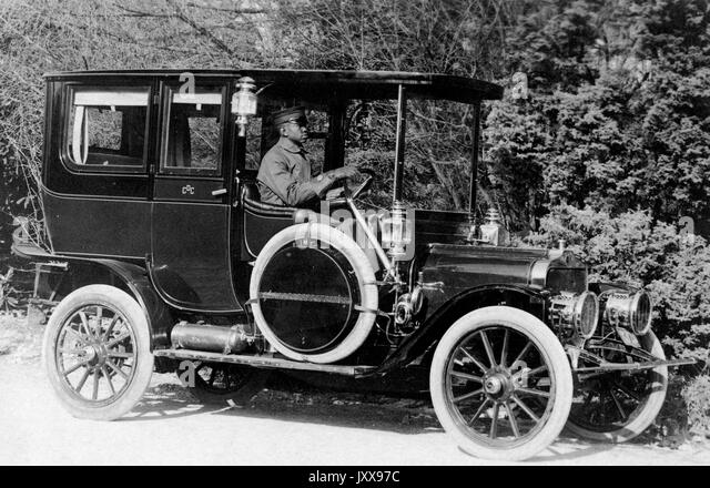 Full length portrait of an African American man driving a car outdoors, wearing a chauffeur's hat, postcard - Stock Image