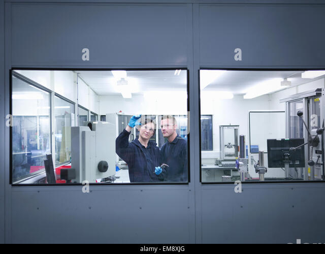 Engineers inspecting automotive parts in clean room of factory - Stock Image