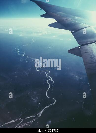 Aerial view of airplane wing with winding river in Russia below as seen from window of All-Nippon Airways Boeing - Stock Image