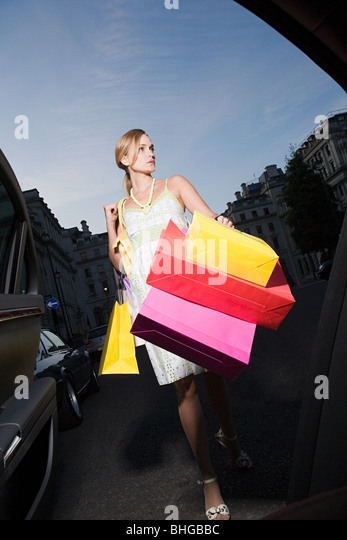 Young woman carrying shopping bags - Stock Image
