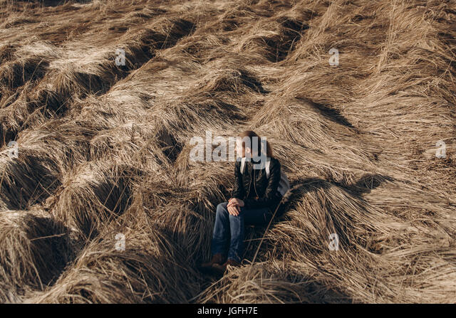 Middle Eastern woman resting in tall grass - Stock Image