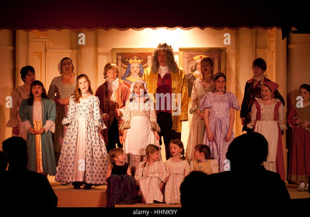 Children and adults on stage for the finale of a village pantomime - Stock Image