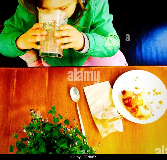 High Angle View Of Girl Drinking Juice By Table - Stock Image