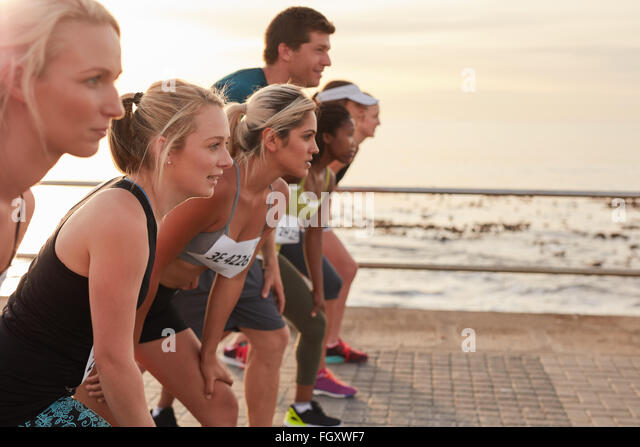Runners standing on the line at the start of a race. Group of young people training for marathon race on road by - Stock Image