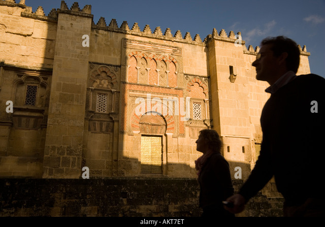 Cordoba Cordoba Province Spain Tourist couple passing by west wall of La Mezquita The Great Mosque - Stock-Bilder